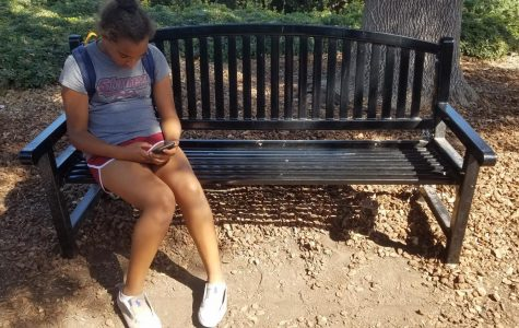Olivia Starr uses her phone on a school bench.