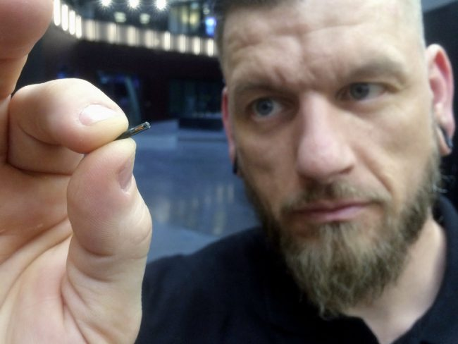 Worker holds up a Biohax microchip.