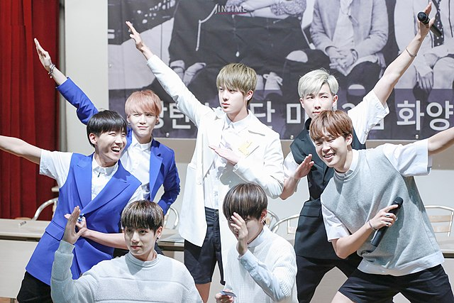 BTS+posing+at+a+fan+signing+event.