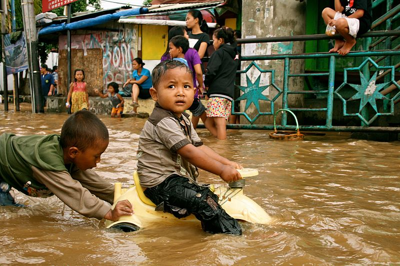Children riding a toy car in midst of the flood.