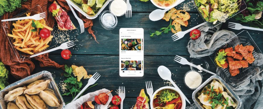Food and utensils surrounding a phone in the middle.