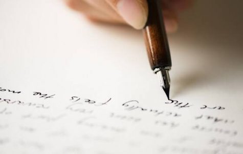 Person writing cursive in black ink.