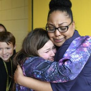 Student hugging her teacher.