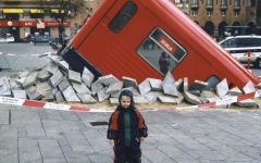 This is an image of a little boy posing in front of a fake bus that crashed into the ground.