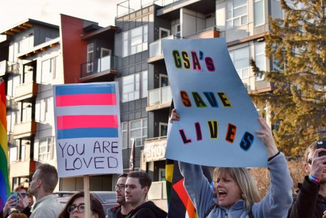 """A group of protesters holds signs reading """"GSA"""